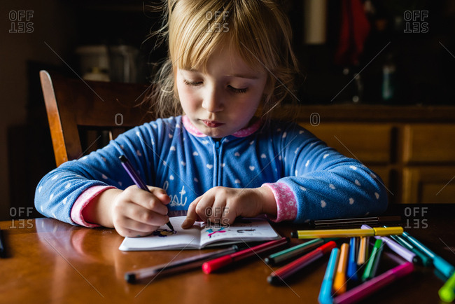 Little girl coloring pictures with markers stock photo - OFFSET