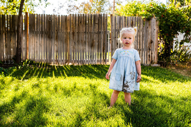 Little girl with muddy face walking in her backyard