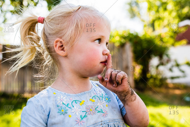 Little muddy girl looking away with finger at her lips