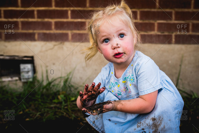 Blonde toddler playing in the mud