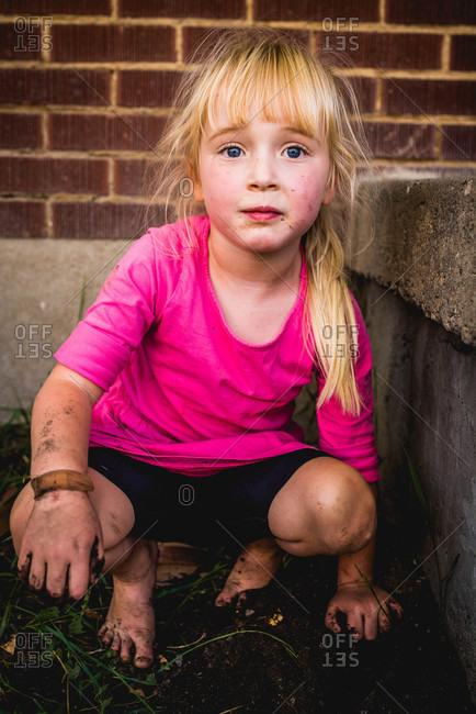 Young girl with bandage on arm playing in mud