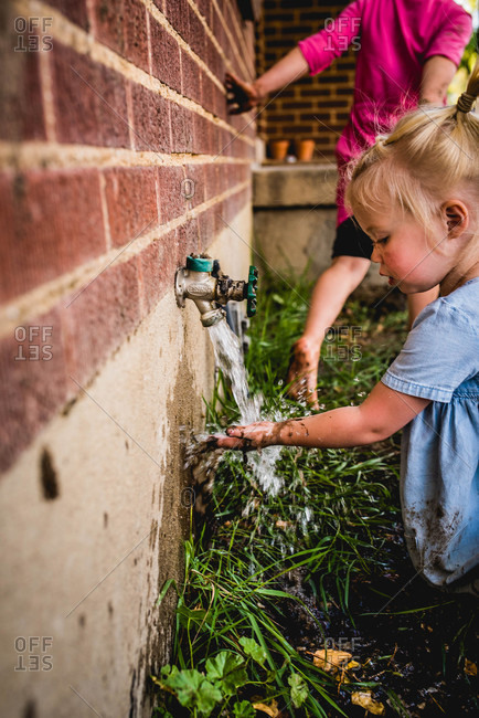 Toddler girl rinsing mud off her hands