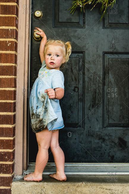 Muddy girl reaching for doorknob
