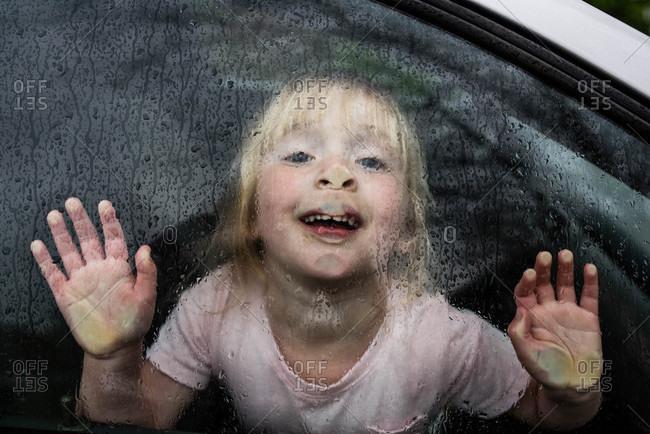 Girl pressing face against rainy car window