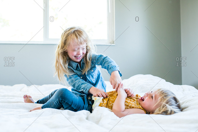 Girl tickling her sister on a bed
