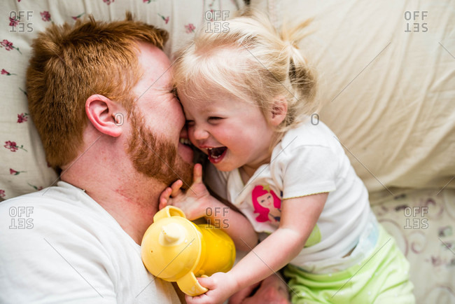 Father and daughter goofing around in bed