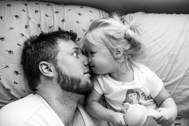 Father and daughter goofing around in bed in black and white