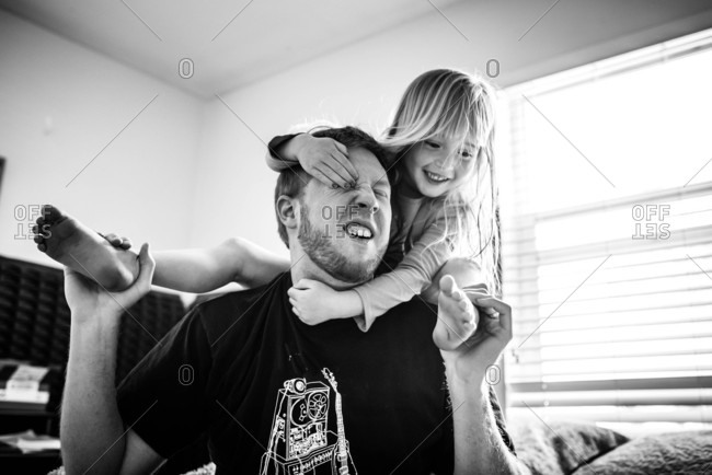 Little girl wrestling with her dad
