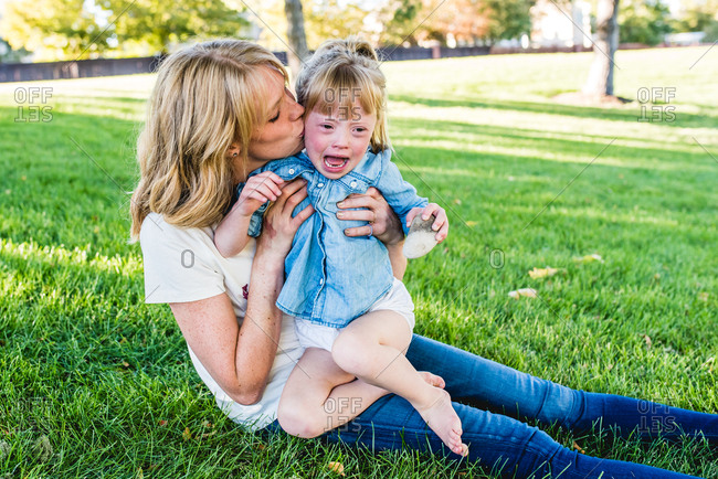 Mother sitting in grass kissing upset daughter's cheek
