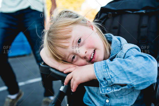Girl with down syndrome resting in a stroller