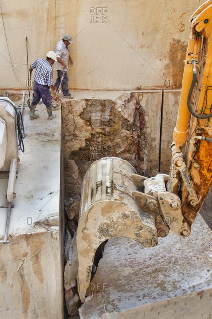 Alentejo, Portugal - October 21, 2014: Men watching excavator in marble quarry