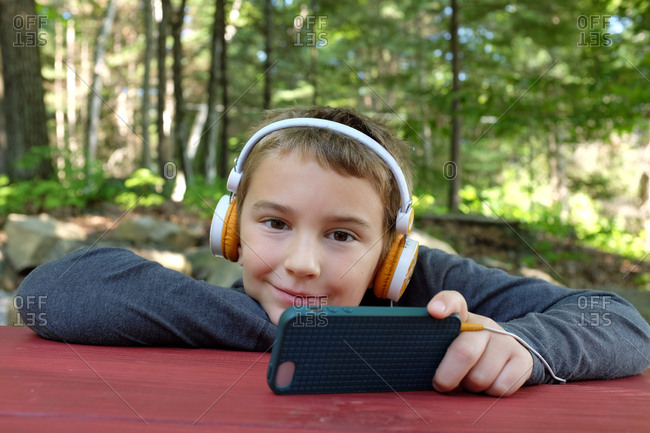 Young boy in headphones uses smartphone while on a camping trip