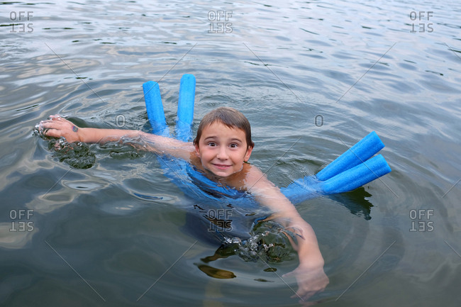 Young boy swimming in a lake with blue noodles