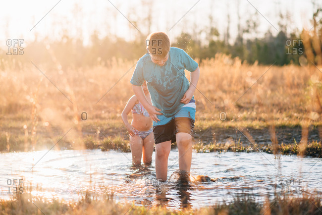 Children wading in mud puddle