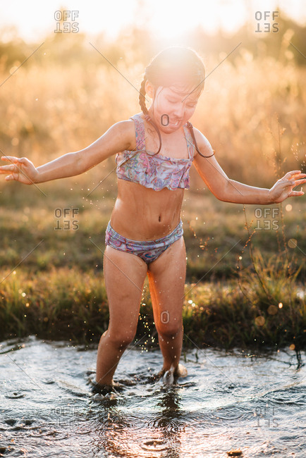 Girl walking in mud puddle at dusk
