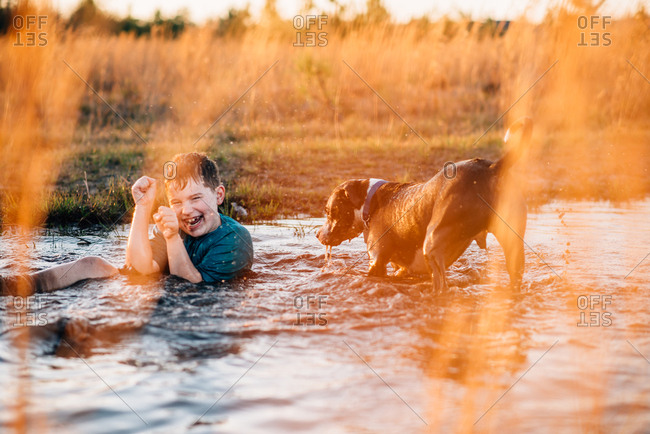 Boy laughs while playing with dog in puddle