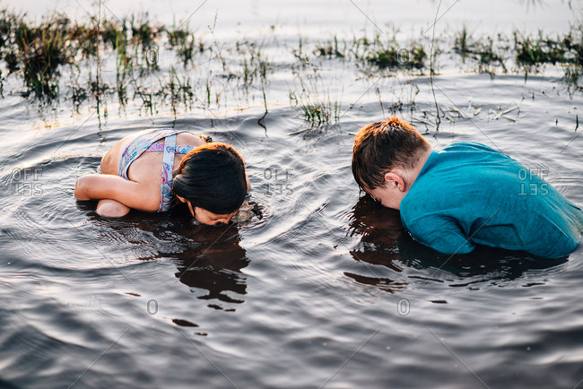 Two children sticking their faces in mud puddle