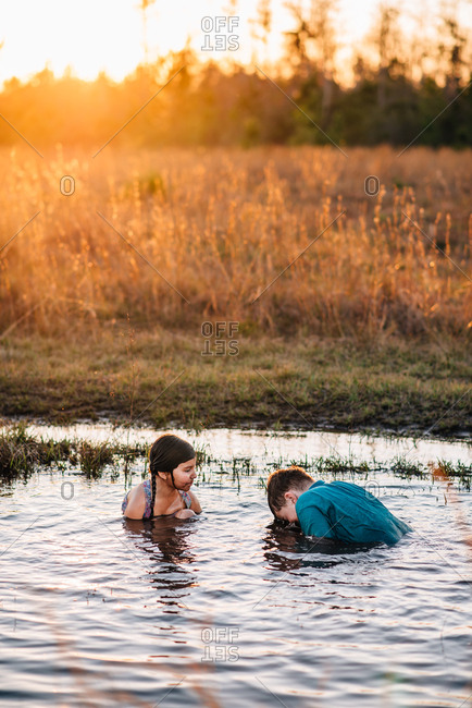 Siblings playing in mud puddle with dog