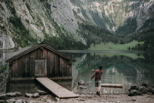 Caucasian man skipping stones in mountain lake