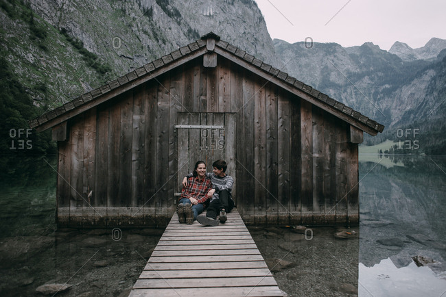 Caucasian couple sitting on dock at remote cabin