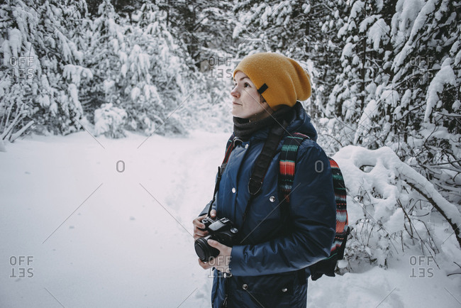 Caucasian woman holding camera in snowy forest