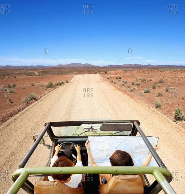 Women driving with map in off-road vehicle