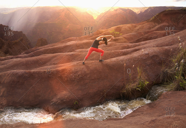 Mixed Race woman stretching arms in volcanic landscape near stream