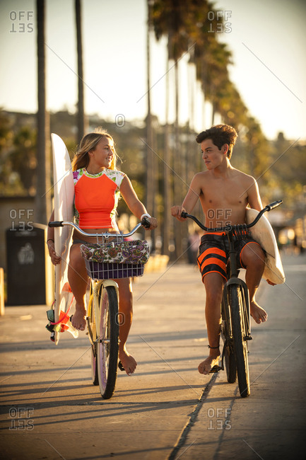 Teenage boy and girl riding bicycles carrying surfboards