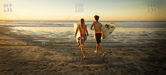 Teenage boy and girl carrying surfboards running to ocean