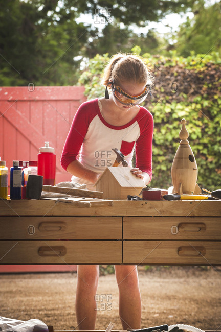 Girl hammering, building birdhouse in garage