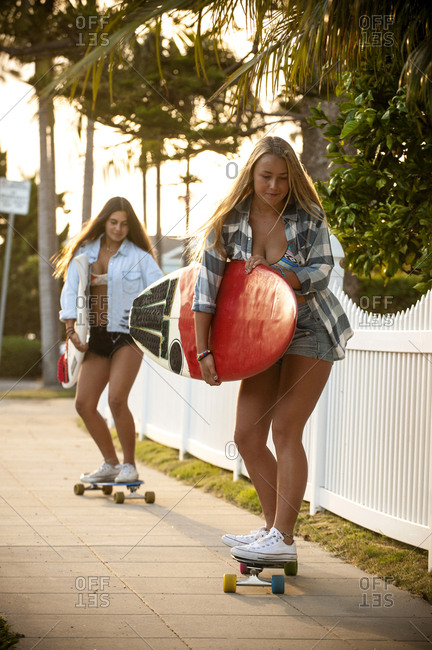 Teenage girls carrying surfboards on skateboards