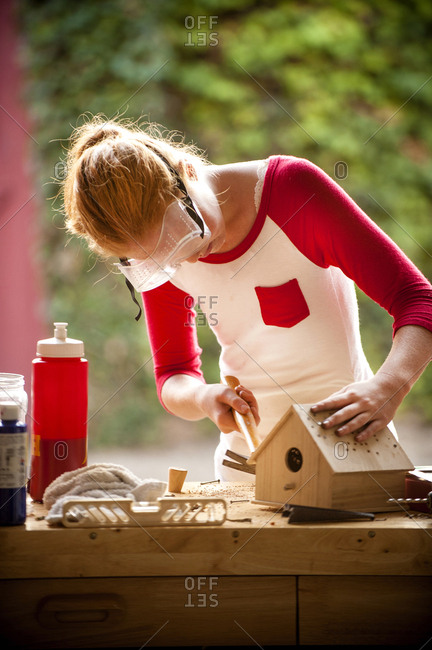 Girl hammering nails into birdhouse