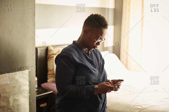 Black woman standing in bedroom texting on cell phone