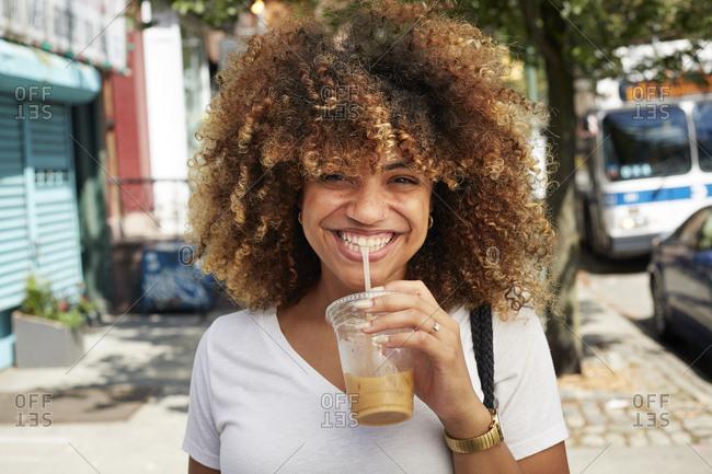 Black woman drinking with straw on city sidewalk