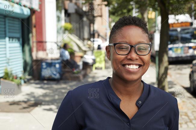 Black woman wearing eyeglasses smiling on city sidewalk