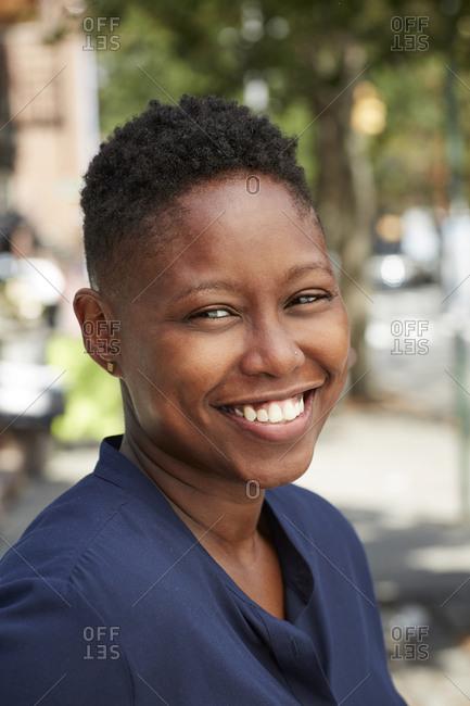 Black woman smiling on city sidewalk