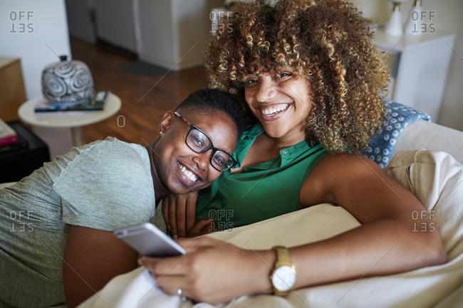 Smiling Black women cuddling on sofa