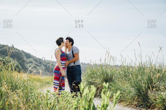 Pregnant lesbian couple kissing on path