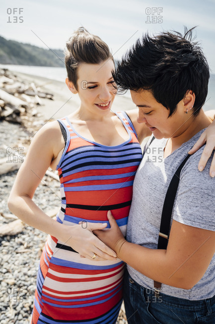Pregnant lesbian couple hugging on beach