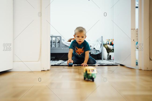 Boy kneeling on floor pushing toy cars