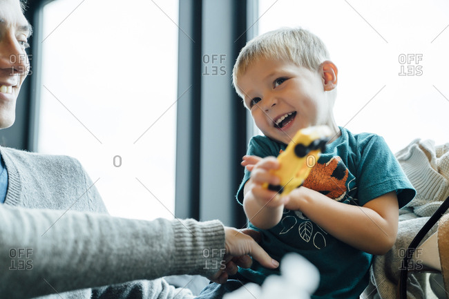 Arm of mother tickling son holding toy car