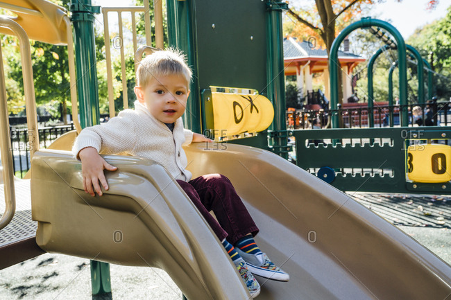 Portrait of Mixed Race boy sitting on playground slide