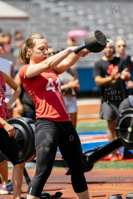 Woman lifting kettle bell outdoors