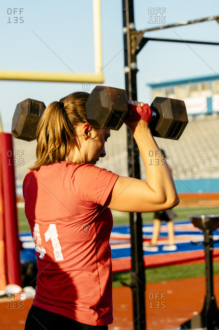 Caucasian woman lifting weights outdoors