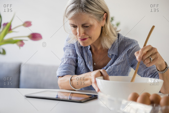 Caucasian woman baking with recipe on digital tablet