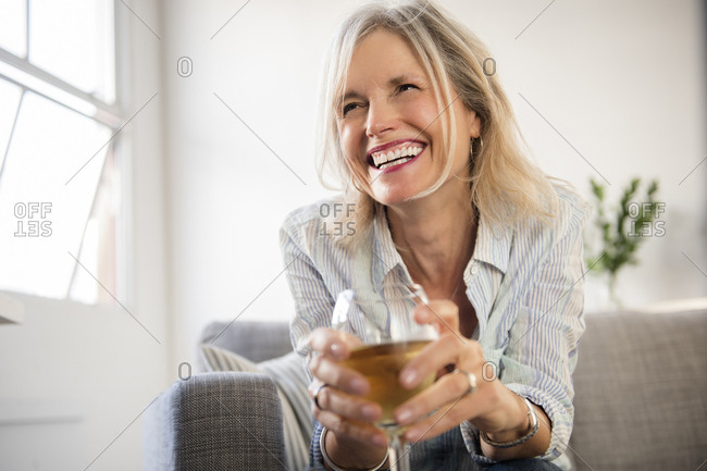 Smiling Caucasian woman sitting on sofa drinking white wine