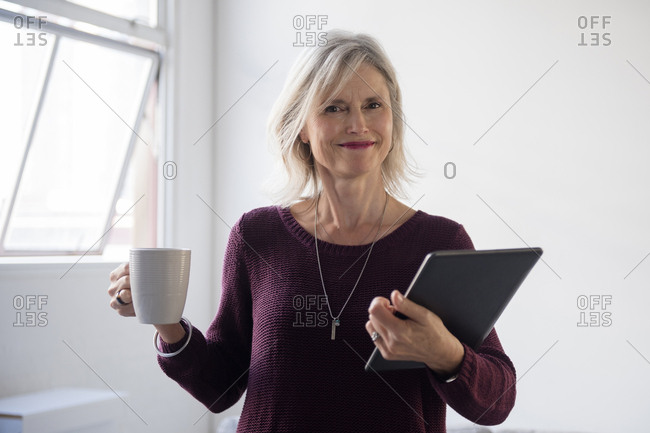 Portrait of Caucasian businesswoman holding coffee cup and digital tablet