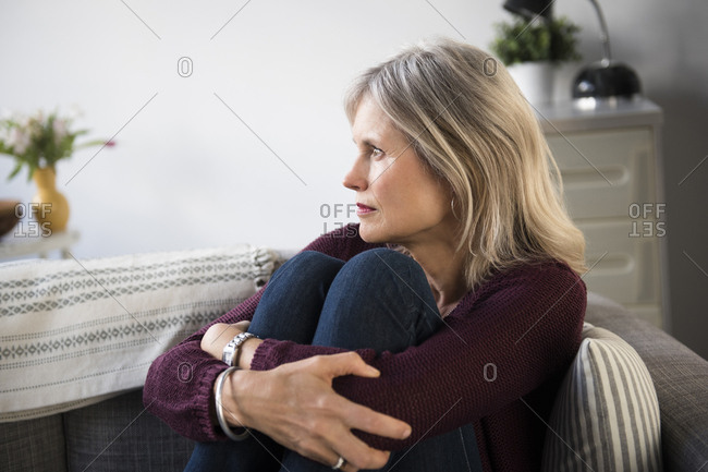 Worrying Caucasian woman hugging legs