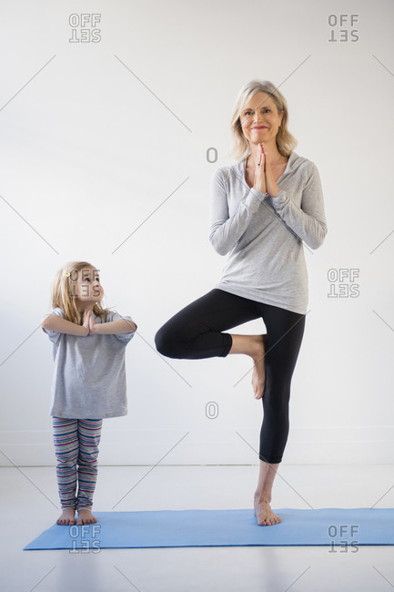 Caucasian granddaughter watching grandmother practicing yoga