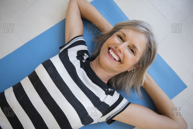 Smiling Caucasian woman laying on exercise mat